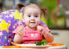 Dziecko siedzi w highchair w kuchni je makaron z warzywami zdjęcie stock