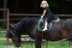Dziecko siedzi w jeźdza comberze na zwierzę plecy obraz stock