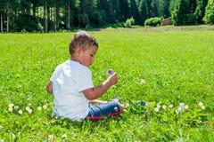 Dziecko siedzący na gazonie Obrazy Stock