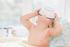 Dziecko stawia puchar na jego głowie Zdjęcia Royalty Free
