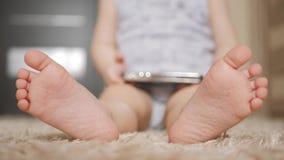 Dziecko stopa przy białym dywanem, zakończenie w górę zbiory