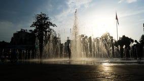 Dziecko sylwetki bawi? si? w miasto fontannie na letnim dniu 4K zbiory