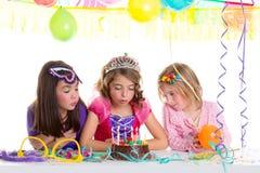 Dziecko szczęśliwe dziewczyny dmucha przyjęcie urodzinowe tort Fotografia Stock