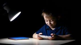 Dziecko szczęśliwie ogląda kreskówkę w domu przy nocą używać smartphone i uśmiechy, siedzi przy stołem zaświecającym lampą