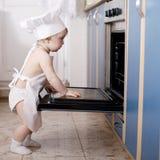 Dziecko szefa kuchni kucharzi w piekarnika jedzeniu