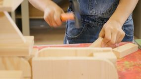 Dziecko sztuka przy rzemiosło warsztatem Śliczna chłopiec młotkuje gwoździa zbliżenia strzał Chłopiec pomaga jego ojca o domu zbiory wideo