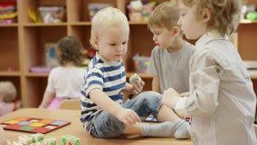 Dziecko sztuka w dziecinu, jeden chłopiec wspinał się na stole i trzymać sześcian drugi chłopiec próbująca podnosić w górę sześci zbiory