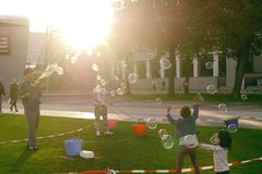 Dziecko sztuka z wielkimi mydlanymi bąblami na zielonym gazonie blisko V Obrazy Royalty Free