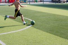 Dziecko sztuki futbol w gazonie obrazy stock