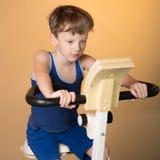 Dziecko trenuje na stacjonarnym rowerze Zdrowy Styl życia Fotografia Stock