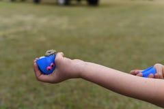 Dziecko trzyma błękitnego plastikowego jajko faszeruje z pieniądze podczas Wielkanocnego jajka polowania obraz stock