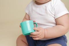 Dziecko Trzyma filiżankę, łasowanie lub Pić, zdjęcia stock