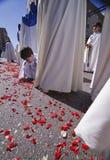 Dziecko trzyma mlejących różanych płatki podczas Świętego tygodnia korowodu Fotografia Stock