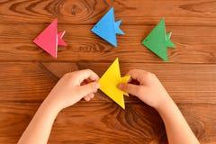 Dziecko trzyma origami ryba Set kolorowa origami ryba na drewnianym stole Zdjęcie Stock