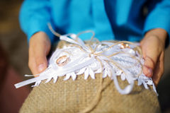 Dziecko trzyma poduszkę z obrączkami ślubnymi na nim Zdjęcie Stock