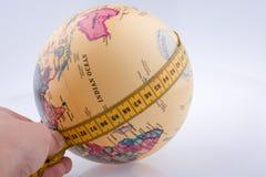 Dziecko trzyma pomiarowej taśmy wokoło kuli ziemskiej Obraz Stock