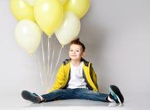 Dziecko trzyma wiązkę balony zostaje na kolanie nad białym tłem zdjęcia royalty free