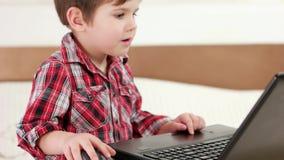 Dziecko używa laptop, chłopiec bawić się gry komputerowe używać touchpad i radio myszy, przyrząda zdjęcie wideo