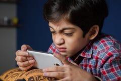 Dziecko używa telefon z śmiesznym wyrażeniem Obrazy Royalty Free