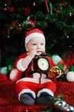 Dziecko ubierający jako Święty Mikołaj objadania zębów zegaru alarm CH Obrazy Stock