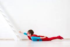 Dziecko ubierający jako nadczłowiek w lot pozyci obrazy stock