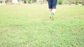 Dziecko utrzymuje futbolowy na zielonej trawie z bliska zbiory
