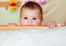 Dziecko w łóżku polowym bawić się peekaboo i ssa łóżko polowe poręcze Fotografia Stock