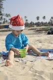 Dziecko w Święty Mikołaj odziewa, boże narodzenia na tropikalnym oceanie był Zdjęcia Royalty Free
