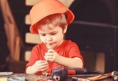 Dziecko w ciężkim kapeluszu, hełm bawić się z hex czmycha jako budowniczy lub naprawiacz handcrafting, Berbeć na ruchliwie twarzy obrazy stock