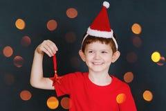 Dziecko w czerwonej koszulce i Santa kapeluszu trzyma błyskotliwą gwiazdę, i Zdjęcia Stock