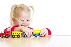 Dziecko w eyeglasses bawić się zabawka pociąg odizolowywającego Fotografia Stock