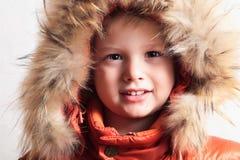 Dziecko w futerkowej kapiszonu i pomarańcze zimy kurtce. moda kid.children.close-up Obrazy Royalty Free