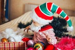Dziecko w gnomów kapeluszowych bożych narodzeniach otwiera jego boże narodzenie teraźniejszość Obraz Royalty Free