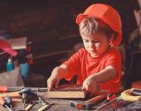 Dziecko w hełma śliczny bawić się jako budowniczy, naprawiacz, naprawianie lub handcrafting, Berbeć na ruchliwie twarzy bawić się zdjęcia stock