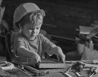 Dziecko w hełma śliczny bawić się jako budowniczy, naprawiacz, naprawianie lub handcrafting, Berbeć na ruchliwie twarzy bawić się obrazy stock