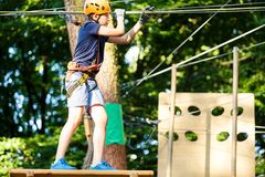 Dziecko w lasowym przygoda parku Dzieciak w pomarańczowym hełmie i błękitne t koszulowe wspinaczki na wysokim linowym śladzie Zwi zdjęcie stock