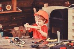 Dziecko w he?ma ?liczny bawi? si? jako budowniczy, naprawiacz, naprawianie lub handcrafting, Handcrafting poj?cie Berbe? na ruchl zdjęcie stock