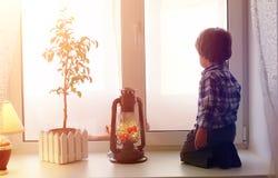 Dziecko w nowym roku patrzeje out okno Dzieci są waiti Fotografia Royalty Free