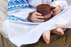 Dziecko w obywatelu odziewa chwyty wewnątrz wręcza glinianego kubek z mlekiem jedzenie wiejski Fotografia Royalty Free