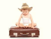 Dziecko w słomianego lata kapeluszowym obsiadaniu na walizce Zdjęcia Stock