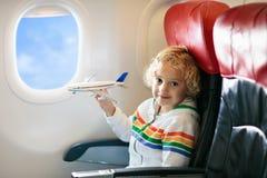 Dziecko w samolocie Dzieciak w lotniczego samolotu obsiadaniu w nadokiennym siedzeniu Lot rozrywka dla dzieciaków Podróżować z mł fotografia stock