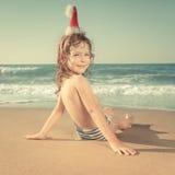 Dziecko w Santa kapeluszu przy plażą Fotografia Stock
