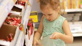 Dziecko w supermarkecie kupuje cukierki i cukierki Robić zakupy sklepu magazyn zbiory wideo