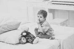 Dziecko w sypialni z cisza gestem Dzieciak stawia mokiet niedźwiadkowe pobliskie poduszki i budzika, luksusowy wewnętrzny tło Cza zdjęcia stock