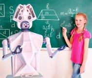 Dziecko w wieku szkolnym i ai robota writing na blackboard w sala lekcyjnej zdjęcia royalty free