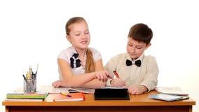 Dziecko w wieku szkolnym siedzi robić i stołem zbiory