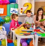Dziecko w wieku szkolnym z nożycami w dzieciakach wręczają rozcięcie papier zdjęcie stock