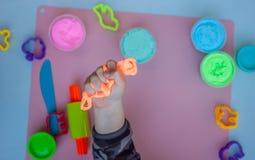 Dziecko wręcza utrzymywać jaskrawego pomarańczowego kawałek plastelina Obraz Royalty Free
