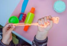 Dziecko wręcza utrzymywać jaskrawego pomarańczowego kawałek plastelina Obrazy Stock