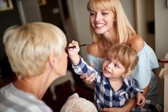 Dziecko wypięknia jej uroczystej mamy z makeup obraz royalty free